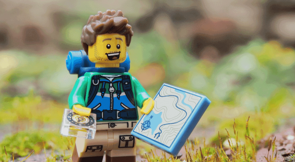 Lego man geocaching with his compass and map