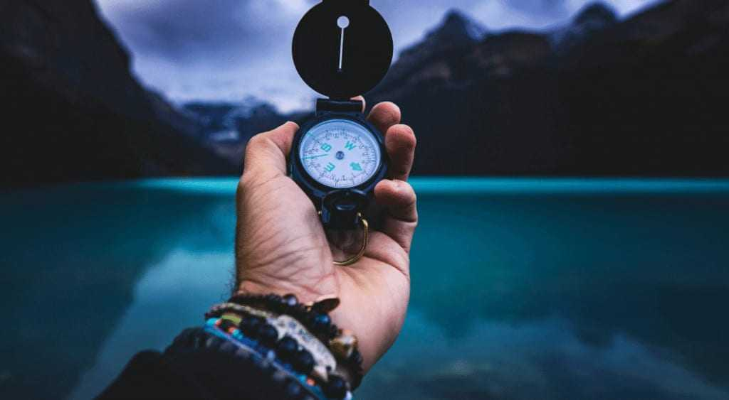 Man holds a compass by a lake