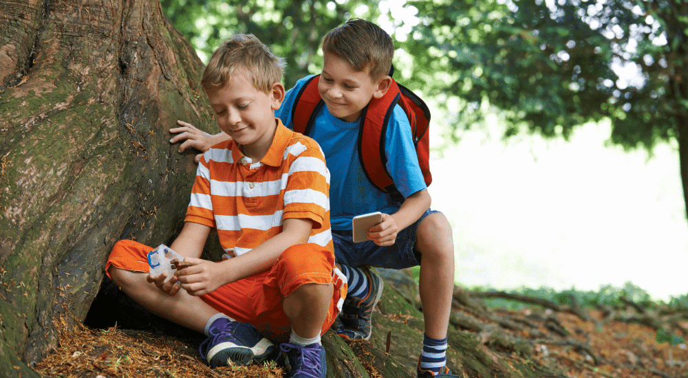 Two boys find a geocache under a tree